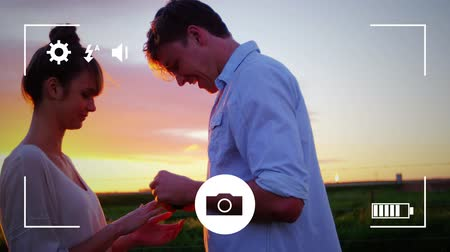 modo : Animation of a side view of a young Caucasian man proposing to a young Caucasian woman at sunset, seen on a screen of a smartphone in picture mode with icons in the foreground Stock Footage