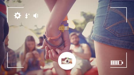 redőnyök : Animation of a rear view close up of a young Caucasian man and woman holding hands with their friends in the background, seen on a screen of a smartphone in picture mode with icons in the foreground Stock mozgókép