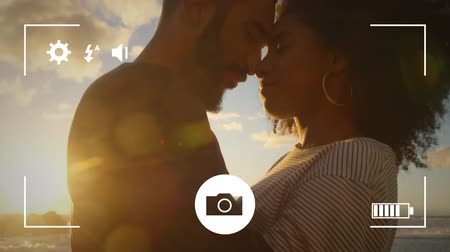 redőnyök : Animation of a side view close up of a young mixed race man and woman on a beach, seen on a screen of a smartphone in picture mode with icons in the foreground