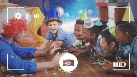 companionship : Animation of a group of pre teen multi-ethnic children in party hats and a clown, seen on a screen of a smartphone in picture mode with icons in the foreground