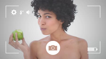 apple icon : Animation of a portrait close up of a young mixed race woman eating an apple, seen on a screen of a smartphone in picture mode with icons in the foreground