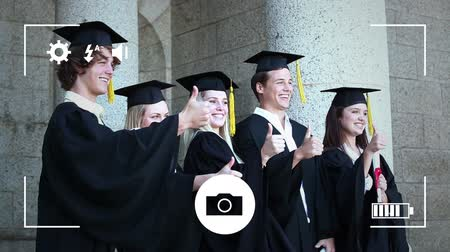 companionship : Animation of a group of Caucasian students graduating and celebrating with thumbs up, seen on a screen of a smartphone in picture mode with icons in the foreground