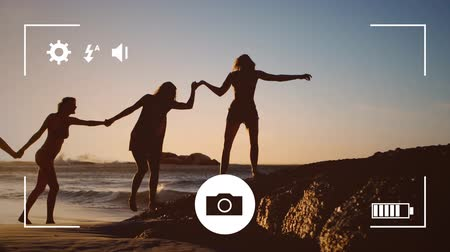 memories : Animation of silhouettes of young female friends holding hands on a beach, seen on a screen of a smartphone in picture mode with icons in the foreground