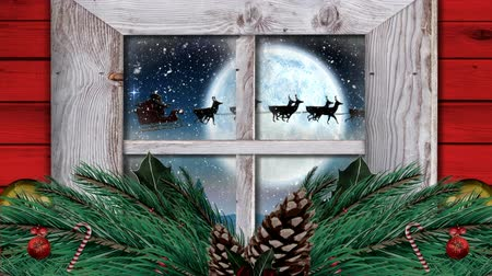 sob : Animation of winter scenery seen through window, with Santa Claus in sleigh being pulled by reindeers, snowfall, moon and baubles, fir tree Dostupné videozáznamy