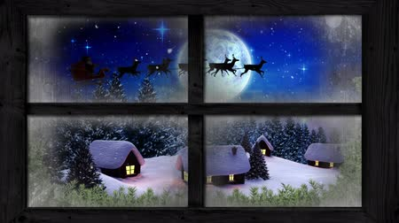 soğuk : Animation of winter scenery seen through window, with Santa Claus in sleigh being pulled by reindeers, snowfall, moon, houses and fir trees Stok Video