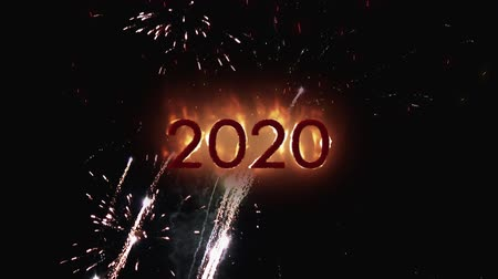 yirmi : Animation of the number 2020 in flames with fireworks on a black background Stok Video