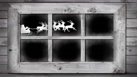 légköri : Animation of winter scenery seen through window, with a white silhouette of Santa Claus in sleigh being pulled by reindeers on black background Stock mozgókép
