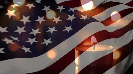 saygı : Animation of lit candles burning with a US flag billowing in the background
