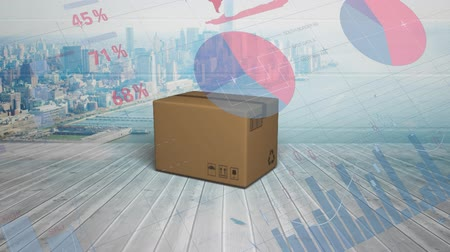 visão global : Animation of cardboard box falling on to wooden floor with charts and graphs and cityscape in the background Stock Footage