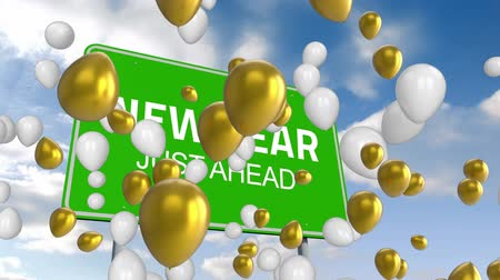 csak : Animation of the words New Year Just Ahead on a green road sign, white and gold balloons floating with blue sky and clouds in the background