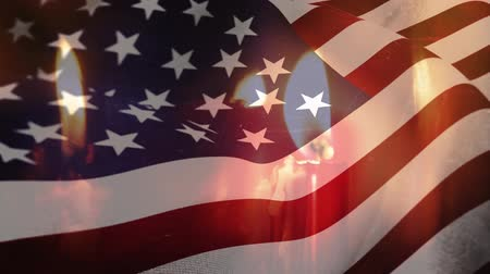 dag van de arbeid : Animation of lit candles burning with a US flag billowing in the background