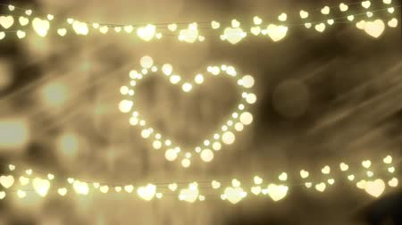 heart shaped : Animation of a Christmas decoration with a heart and strings of glowing heart shaped fairy lights on a defocused background Stock Footage