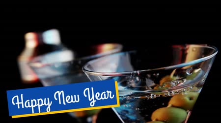 seasons changing : Animation of the words Happy New Year in white letters on a blue banner and with olives dropping into a cocktail glass in the background