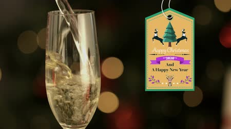 champagne flute : Animation of the words Happy Christmas and A Happy New Year 2020 written on a label decorated with reindeers and Christmas tree with champagne glass and defocused lights in the background Stock Footage