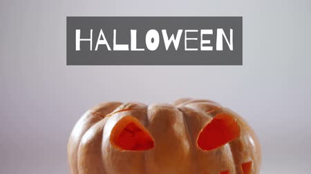 vytesaný : Animation of the word Halloween in white letters on a grey banner with carved pumpkin in the background