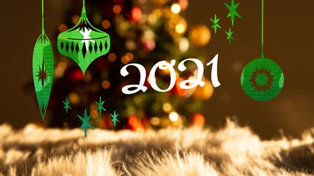 changing lights : Animation of number 2021 written in white letters with Christmas baubles drawn in green, in front of defocused Christmas tree