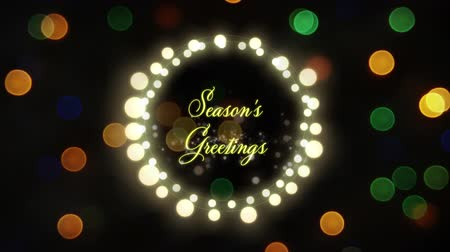 christmas spirit : Animation of the words Seasons Greetings in yellow letters in a round frame of glowing fairy lights with flickering defocused lights in the background Stock Footage