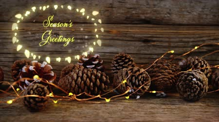 christmas spirit : Animation of the words Seasons Greetings in an oval frame of glowing fairy lights with pine cones in the background Stock Footage