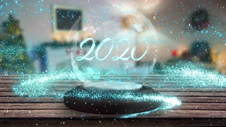 komet : Animation of number 2020  written in white on a snow globe, blue shooting star and Christmas tree in the background
