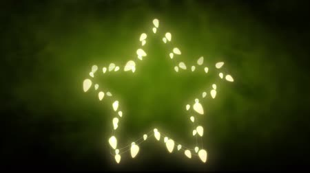 christmas spirit : Animation of a Christmas decoration with a star of glowing fairy lights on a green background