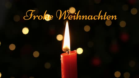 changing lights : Animation of the words Frohe Weihnachten written in orange with lit candle and flickering lights in the background