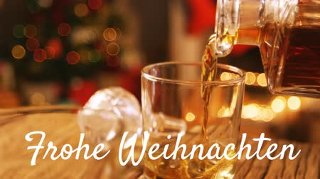 seasons changing : Animation of the words Frohe Weihnachten written in white with drink being poured with Christmas tree in the background Stock Footage