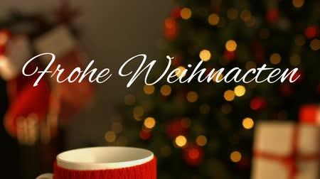 changing lights : Animation of the words Frohe Weihnachten written in white with mug and plate of cookies with Christmas tree in the background Stock Footage