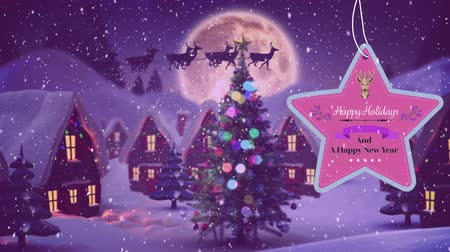 mille : Animation of the words Happy Holidays and A Happy New Year written on a pink star shaped label decorated with a reindeer head and purple leaves, with a decorated Christmas tree and a countryside night scene with cottages, falling snow and a full moon in t Vidéos Libres De Droits