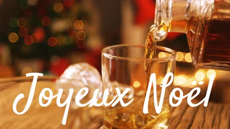 christmas tree with lights : Animation of the words Joyeux Noᅢᆱl written in white with drink being poured with Christmas tree in the background