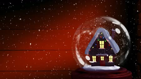 changing lights : Animation of a snow covered cottage with Christmas lights on it in a snow globe, with wooden planks at night and falling snow in the background