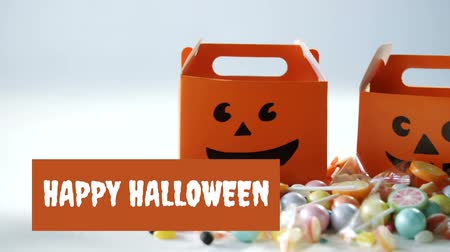 текст : Animation of the words Happy Halloween written in white on an orange banner with a orange pumpkin face cardboard baskets and piles of sweets in the background Стоковые видеозаписи