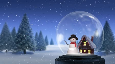 seasons changing : Animation of a snowman standing beside a snow covered cottage in a snow globe, with a countryside winter scene with Christmas trees and falling snow in the background