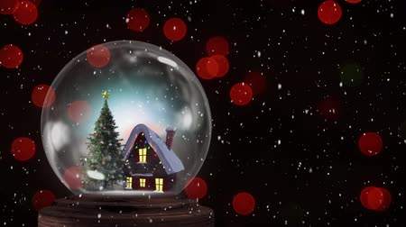 changing lights : Animation of a snow covered cottage and a decorated Christmas tree in a snow globe, with circles of red defocussed light and falling snow against a black background Stock Footage