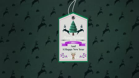 desenli : Animation of the words Happy Holidays 2021 and A Happy New Year written on a beige label decorated with reindeer and a Christmas tree, hanging in front of green wallpaper patterned with jumping reindeer and bells in the background
