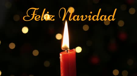 changing lights : Animation of the words Feliz Navidad written in orange with lit candle and flickering lights in the background Stock Footage