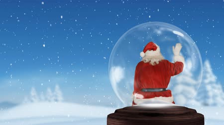 snow globe : Animation of the rear view of Santa Claus sitting and waving in a snow globe, with snow falling on a countryside landscape and a blue sky in the background Stock Footage