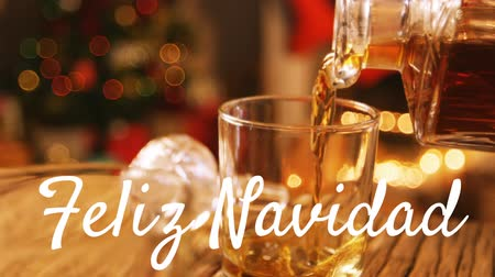 changing lights : Animation of the words Feliz Navidad written in white with drink being poured with Christmas tree in the background