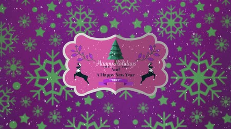 seasons changing : Animation of the words Happy Holidays and A Happy New Year 2021 written on a pink label decorated with reindeer and a Christmas tree, with falling snow and green snowflakes on a purple background Stock Footage