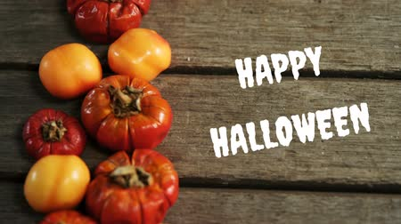 hallows : Animation of the words Happy Halloween written in white with dried yellow and red seasonal vegetables on wooden boards in the background Stock Footage