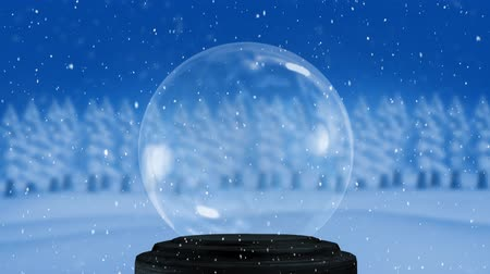snow globe : Animation of an empty snow globe, with countryside and a row of snow covered trees with falling snow against a blue sky in the background
