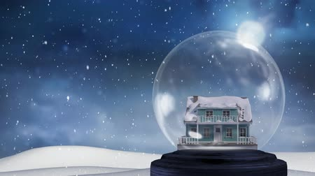 seasons changing : Animation of a snow covered house in a snow globe, with snow covered ground, falling snow and a full moon in a dusk sky in the background