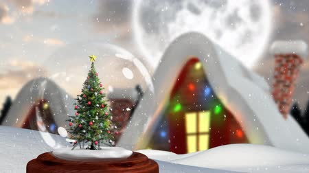 changing lights : Animation of a decorated Christmas tree in a snow globe, with falling snow and a snow covered cottage with Christmas lights on it in the background Stock Footage