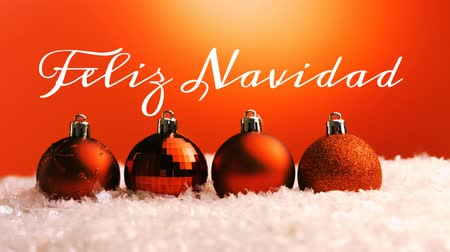 önemsiz şey : Animation of the words Feliz Navidad written in white with red Christmas baubles in the background