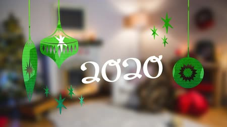changing lights : Animation of number 2020 written in white with Christmas baubles drawn in green, in front of defocused room at Christmas time Stock Footage