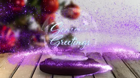 seasons changing : Animation of the words Seasons Greetings written in blue letters on a snow globe, purple shooting star and Christmas tree in the background