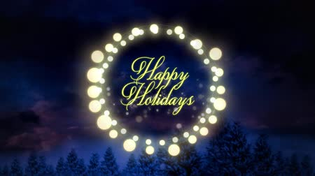 精神 : Animation of the words Happy Holidays written in yellow letters in a round frame of glowing fairy lights on blue background