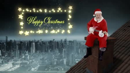 guitarrista : Animation of the words Happy Christmas in a rectangular frame of glowing star shaped fairy lights with Santa Claus playing guitar on roof Vídeos