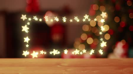 négyszögletes : Animation of a rectangular frame of glowing star shaped fairy lights on a defocused Christmas tree in the background Stock mozgókép