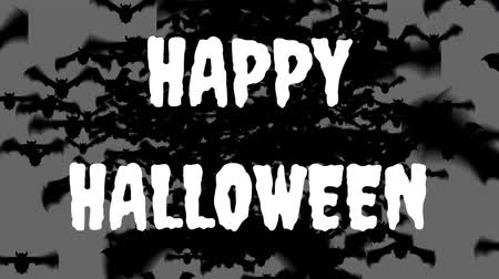 superstition : Animation of the words Happy Halloween written in white with lots of black bats flying to the foreground, on a grey background Stock Footage