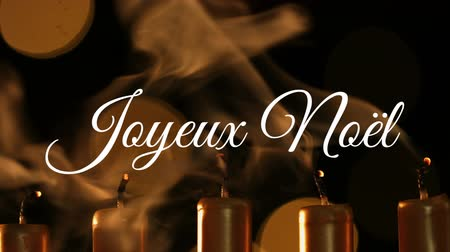 changing lights : Animation of the words Joyeux Noᅢᆱl written in white with candles being blown out and flickering lights in the background
